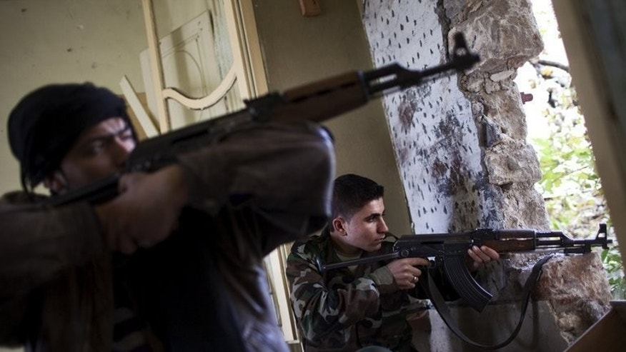 Syrian rebels aim their weapons at regime forces during clashes in Aleppo, on December 21, 2012. Iran has denounced a decision by Western and Arab countries to send weapons to Syrian rebels fighting the regime of President Bashar al-Assad, according to the official IRNA news agency.