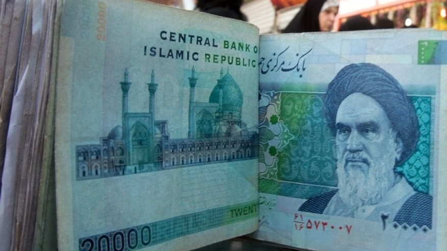 A money dealer counts Iranian rial bank notes bearing a portrait of the late founder of the Islamic Republic of Iran, Ayatollah Ruhollah Khomeini, at an exchange office in Baghdad on February 3, 2012. The rial has strengthened by more than 15 percent against the dollar since the victory of moderate Hassan Rowhani who was elected president more than a week ago, reports said.