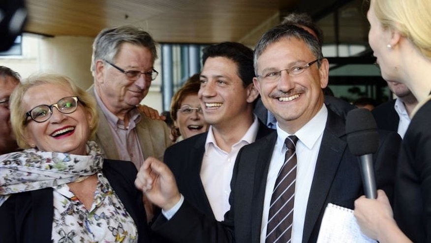Jean-Louis Costes (2nd R), candidate for France's main centre-right UMP party for a by-election for the National Assembly, speaks to the media on June 23, 2013, in Fumel, after being elected deputy. The by-election had been seen as a test of a recent revival in the fortunes of the far-right Front National (FN), officials said.