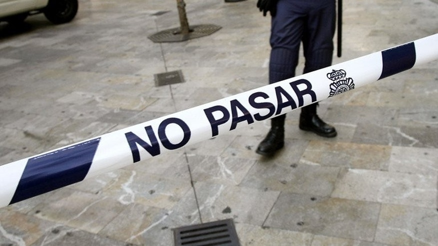 Spanish security personnel man a police cordon. A woman has been arrested for attempted murder after her two-day old baby was discovered inside a building's drains in Alicante and painstakingly rescued by firefighters.
