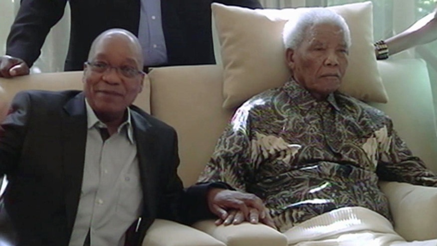 April 29, 2013: In this image taken from video, South African President Jacob Zuma, left, sits with the ailing anti-apartheid icon Nelson Mandela is filmed more than three weeks after being released from hospital.