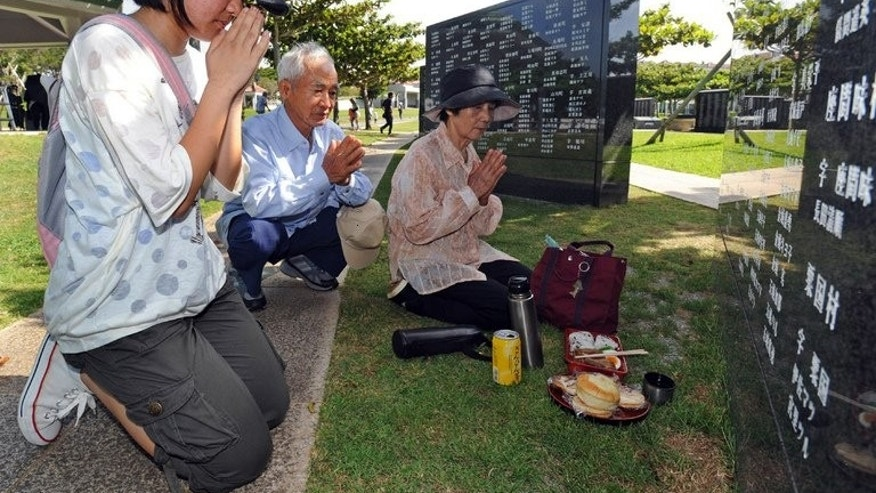"Relatives of victims killed at the 'Battle of Okinawa' pray during a memorial service at the Peace Memorial Park in Itoman, on June 23, 2013. Okinawa has marked the 68th anniversary of a bloody World War II battle, with Japan's prime minister vowing to ""lighten the burden"" of local residents opposed to a heavy US military presence on the southern Japanese island."