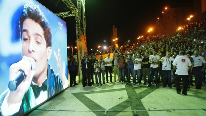 Palestinians watch the performance of Palestinian singer Mohammed Assaf, a contestant in a regional TV singing contest, on a large screen in the West Bank city of Nablus, Saturday, June 21, 2013. Palestinians relished a rare moment of pride and national unity Saturday after a 23-year-old wedding singer from a refugee camp in the Gaza Strip won Arab Idol, a regional TV singing contest watched by millions of people. (AP Photo/Nasser Ishtayeh)
