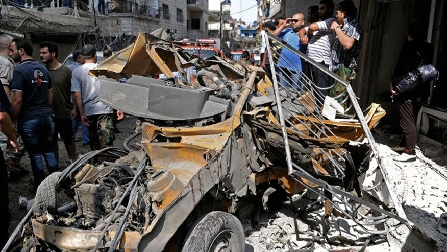 June 23, 2013: In this photo released by the Syrian official news agency SANA, Syrians investigate damages after two suicide bombings hit security compounds in Damascus, Syria.