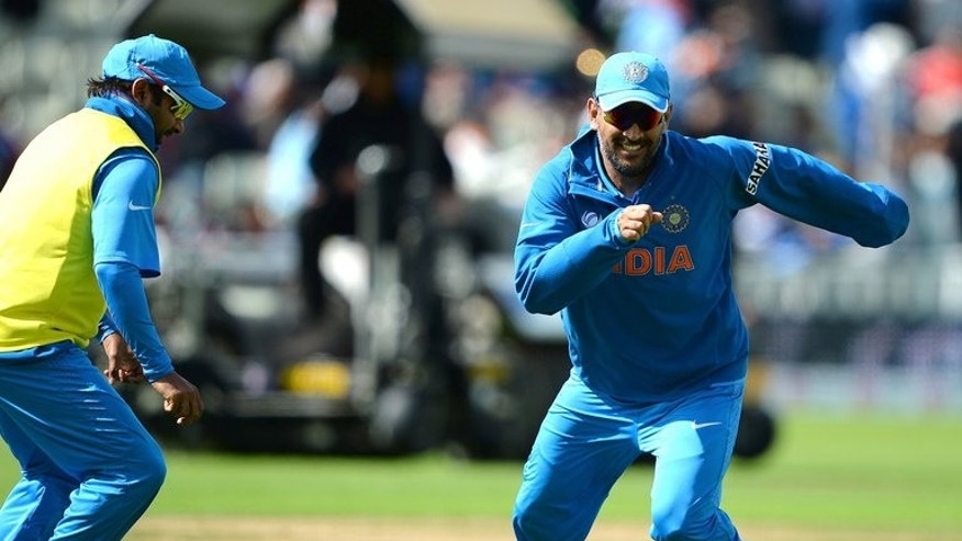 India's Mahendra Singh Dhoni (R) plays football to warm up ahead of their rain-delayed 2013 ICC Champions Trophy final match against England, at Edgbaston in Birmingham, on June 23, 2013.