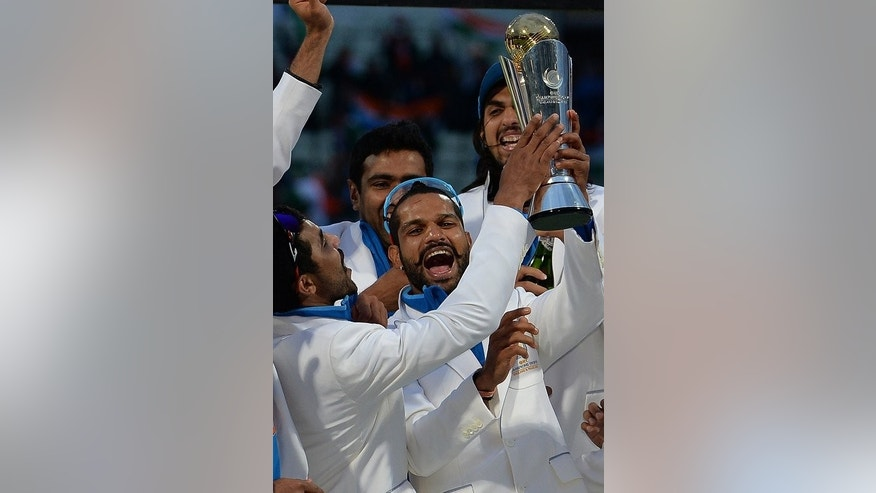 India's Shikhar Dhawan (C) celebrates with the trophy following their victory in the 2013 ICC Champions Trophy final match against England, at Edgbaston in Birmingham, on 23, June 2013. India beat England by five runs.