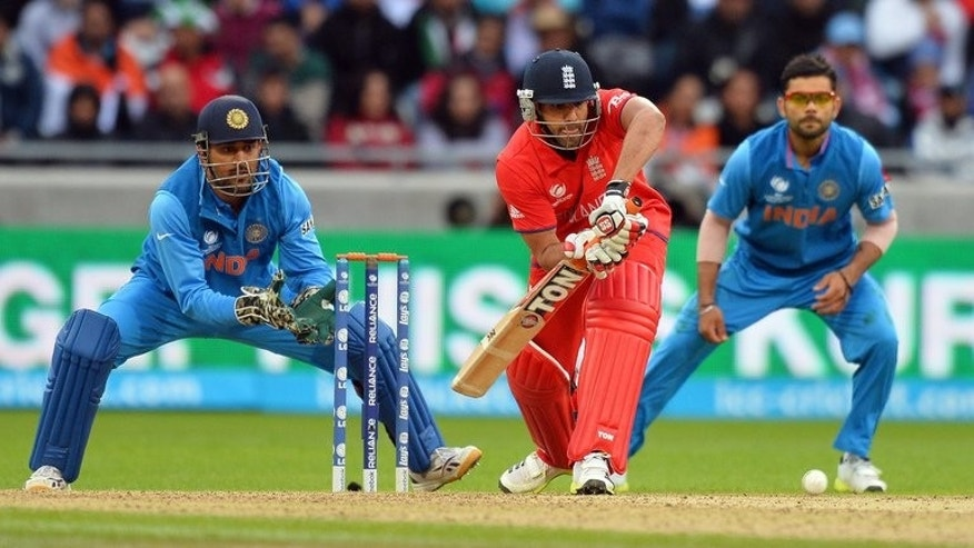 England's Ravi Bopara (C) plays a shot as India's captain Mahendra Singh Dhoni (L) and Virat Kohli look on during their 2013 ICC Champions Trophy final match, at Edgbaston in Birmingham, on June 23, 2013. India beat England by five runs.
