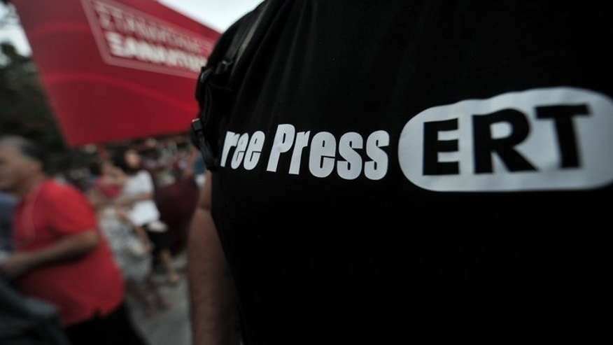 "An opposition supporter wears a ""Free Press ERT"" T-shirt during a rally in Athens, on June 17, 2013. As debate swirls in Greece over the future of public broadcasting, analysts say the abrupt shutdown of state broadcaster ERT is only the latest problem to hit Greece's chaotic media scene."