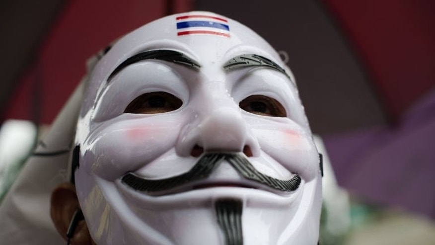 A protester wearing a Guy Fawkes mask attends a rally in Bangkok's shopping district on June 23, 2013. Hundreds of anti-government protesters -- many wearing Guy Fawkes masks -- converged in Bangkok, in a reminder of the kingdom's political divisions.