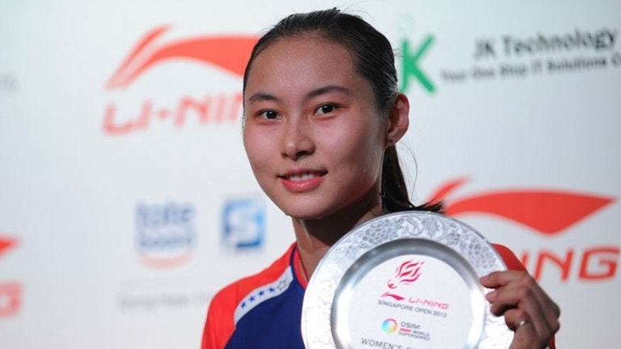 China's Wang Yihan poses with the plaque after winning against compatriot Li Xuerui during their women's singles final badminton match at the Singapore Open on June 23, 2013. Wang won 21-18, 21-12.