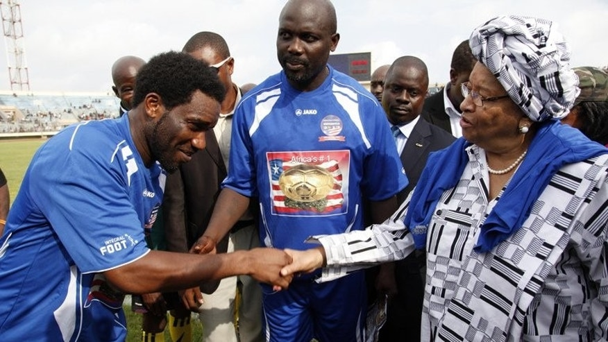 Former football player Jay Jay Ochocha (L) shakes hands with Liberian President Ellen Johnson Sirleaf (R) next to Liberia's former football star George Weah (C) on June 22, 2013. Weah has been joined by legends of the game from across Africa to promote reconciliation in his homeland more than a decade after civil wars which killed 250,000 people.