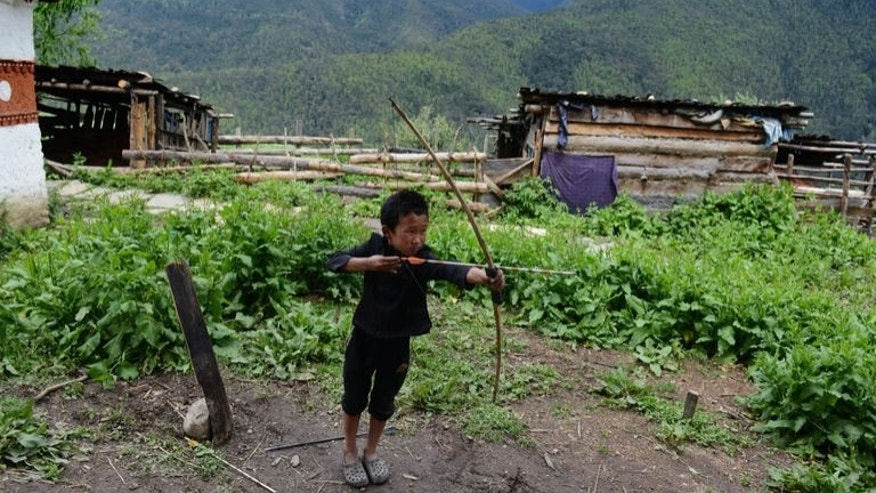 "A child plays with his bow and arrow, in a small village, in mountains near the eastern Bhutanese town of Paro, on June 2, 2013. It is known as ""the last Shangri-La"" -- a remote Himalayan nation, rich in natural beauty and Buddhist culture, where national happiness is prioritised over economic growth."