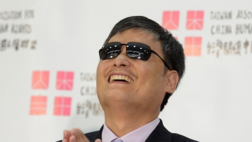 """Chinese dissident Chen Guangcheng gestures during a press conference in Taipei, on June 24, 2013. Chen has urged Taiwan to stand up to China's """"illegitimate"""" communist government, as he visited the self-governing island amid controversy over his future in the United States."""