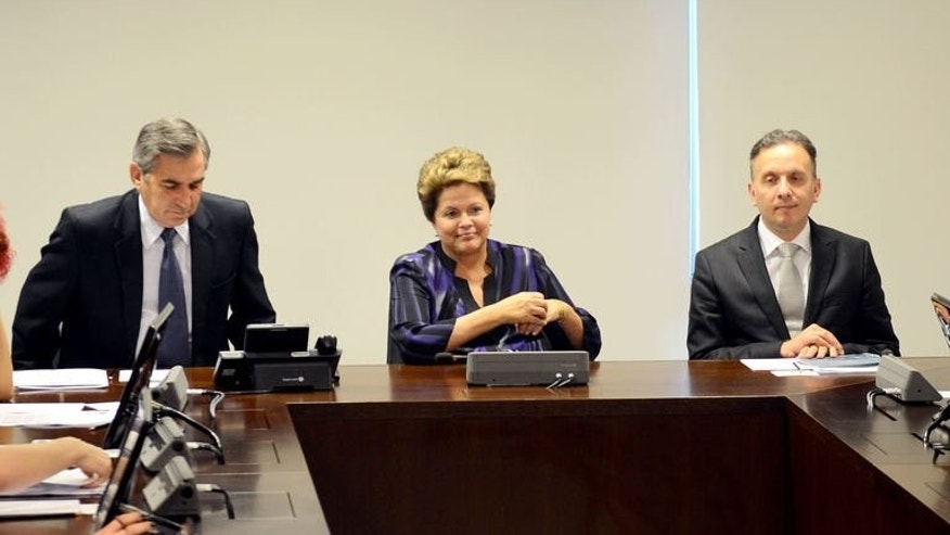 Brazilian President Dilma Rousseff (C), General Secretary of the Presidency Gilberto Carvalho (L) and the Minister of Cities Aguinaldo Ribeiro are seen during a meeting at the Planalto Palace in Brasilia on June 24, 2013. Rousseff on Monday proposed to earmark $25 billion for public transport following massive nationwide street protests over the country's inadequate mass transit system.