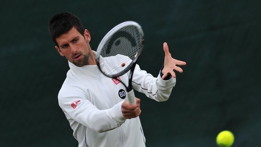 Serbia's Novak Djokovic plays a shot during a training session at Wimbledon on June 23, 2013. Djokovic and Serena Williams will hope to avoid the same fate as Rafael Nadal on Tuesday as Wimbledon comes to terms with one of the most stunning upsets in All England Club history.