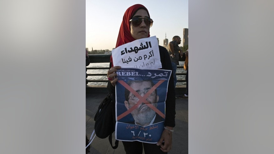 A protester holds a portrait of President Mohamed Morsi with a red X over his face, in Cairo, on June 6, 2013. Morsi's opponents accuse him of concentrating power in the hands of the Muslim Brotherhood and of failing the aspirations for freedom and social justice that inspired the revolution that toppled Hosni Mubarak in 2011.