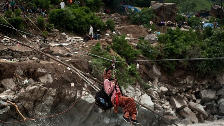 A stranded Indian pilgrim is transported across a river using a rope rescue system, by Indo-Tibetan Border Police (ITBP) personnel in Govind Ghat, on June 23, 2013. Indian priests are planning to cremate hundreds of flood victims, as heavy rains halted the search for thousands of tourists stranded in the devastated Himalayan region.