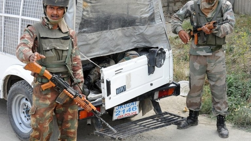 Police stand near the bodies of two Indian army soldiers, lying inside a police vehicle near the scene of an attack by armed rebels, on the outskirts of Srinagar, on June 24, 2013. Prime Minister Manmohan Singh was to pay a landmark visit to troubled Indian Kashmir on Tuesday, a day after heavily-armed militants killed eight soldiers in the deadliest attack in the region for five years.