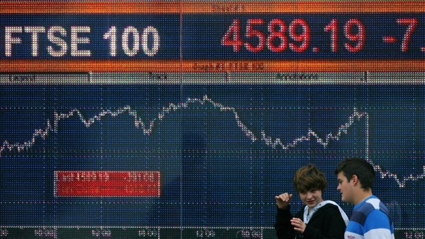 People walk past an electronic sign showing the level of the FTSE 100 in London in October 2008. London shares closed lower on Monday as stock markets fell across the world amid anxiety about a growing credit crunch in China, dealers said.