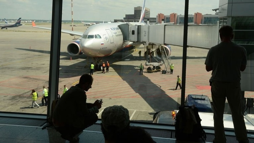 People look the passenger plane, flight SU 150 to Havana, docking to a boarding bridge at the Moscow Sheremetyevo airport on June 24, 2013.