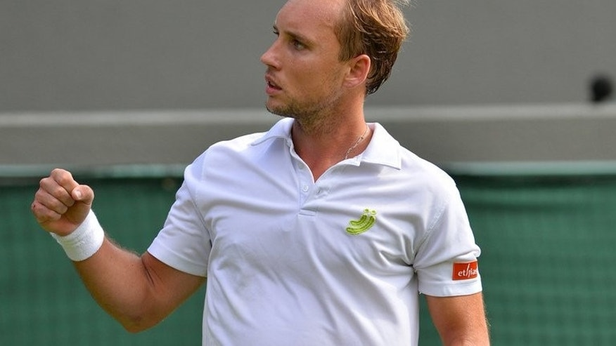 Belgium's Steve Darcis celebrates winning the second set against Spain's Rafael Nadal during their men's first round match on day one of the 2013 Wimbledon Championships tennis tournament at the All England Club in Wimbledon, southwest London, on June 24, 2013.