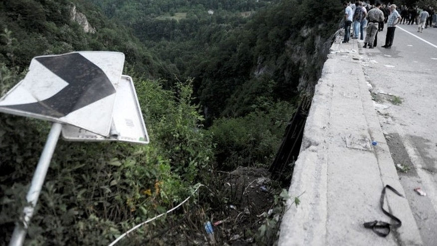 People look at the scene of a bus accident near Grlo, on June 23, 2013. Eighteen Romanians have died and 28 others were injured when their bus crashed in Montenegro in one of the deadliest road accidents the tiny Adriatic republic has seen.