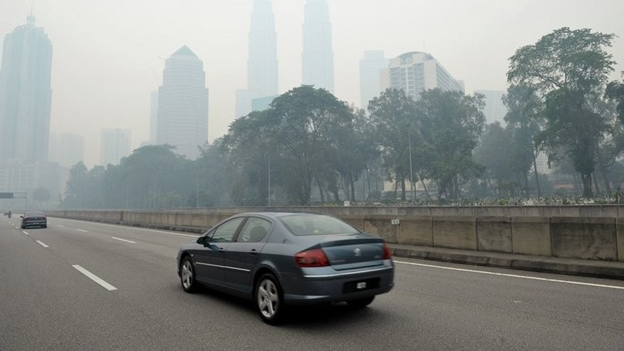 Haze shrouds Malaysia's landmark Petronas Towers in Kuala Lumpur, on June 23, 2013. The thick smog brought on by forest fires in Indonesia has choked parts of Malaysia, prompting the government to declare a state of emergency in two southern districts.