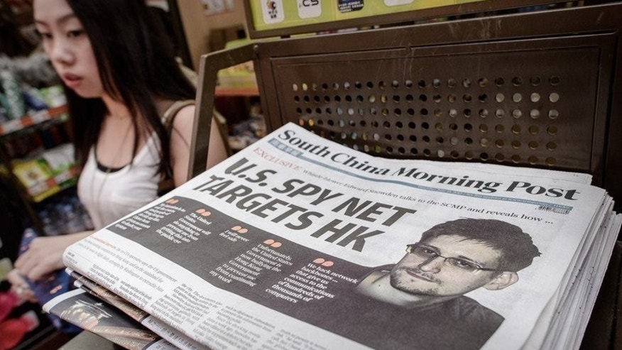 An edition of the South China Morning Post carryies a story of former US spy Edward Snowden (R) in Hong Kong on June 13, 2013. Snowden took up a position at a US government defence contractor specifically to gather evidence on Washington's surveillance programmes, he told the paper in remarks published Tuesday.