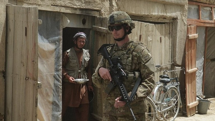 An Afghan civilian looks on as a US soldier patrols the streets in Ghazni, on May 19, 2013. US envoy James Dobbins is set for talks with Afghan President Hamid Karzai in Kabul later Monday, as Washington works to put peace efforts back on track after a dispute over the rebels' new office in Qatar.
