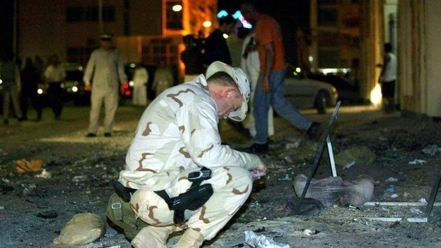"A US Navy officer examines the scene of an explosion near the headquarters of the Navy's Fifth Fleet in Manama on March 24, 2003. The US military has failed to prepare a realistic ""plan B"" if political turmoil forces the closure of the vital naval base in Bahrain, a naval officer argues in a report released Monday."