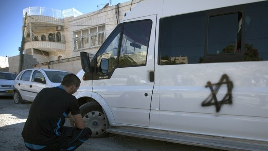 "A Palestinian man looks at the slashed tires of his van which was also sprayed with the Star of David, in the Arab east Jerusalem neighborhood of Beit Hanina, on June 24, 2013. Suspected Jewish extremists punctured the tyres of more than 20 Palestinian cars in east Jerusalem on Monday in the latest apparent ""price tag"" hate crime, police and an AFP correspondent said."
