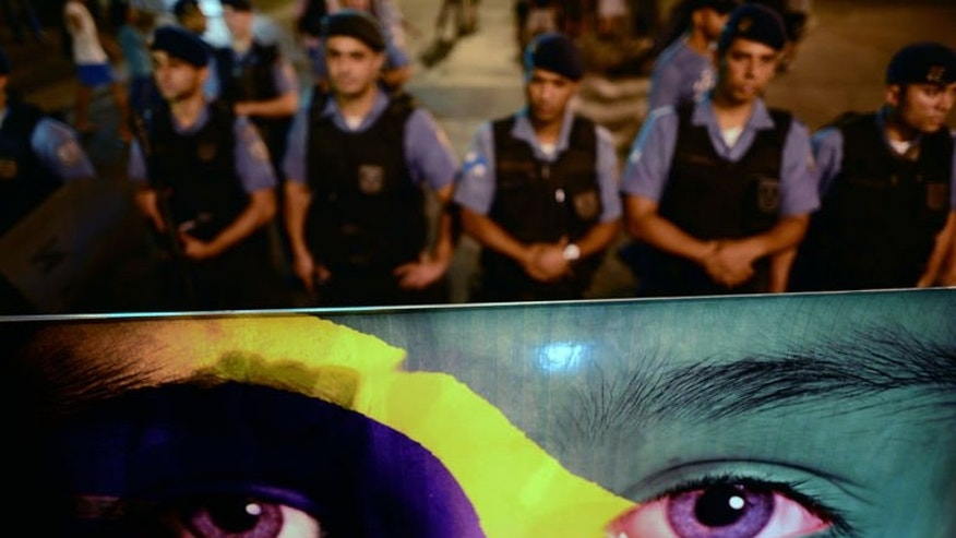 Police officers stand guard as residents of the Rocinha favela demonstrate against against the abuse of power, corruption, higher public transportation fares and the use of public funds to organise international football tournaments, in Rio de Janeiro on June 25, 2013.