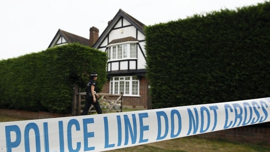British police stand outside the home of Saad and Iqbal al-Hilli in Claygate, in Surrey, southeast England, on September 14, 2012. British police on Tuesday released on bail a suspect and brother of murdered British-Iraqi man, Saad al-Hilli, who was shot dead along with his wife, mother-in-law and a French cyclist in the Alps last year.
