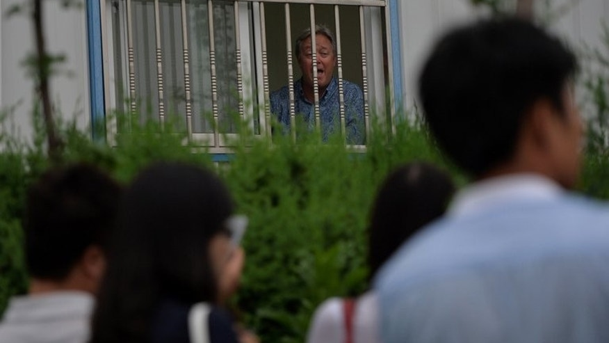 US businessman Chip Starnes stands behind the bars of his office window after being held hostage for five days over a wage dispute at the Specialty Medical Supplies factory in Huairou, Beijing on June 25, 2013. An American factory boss in China held hostage in his office for five days by workers told AFP he won't be released until a labour dispute is resolved and that authorities won't intervene.