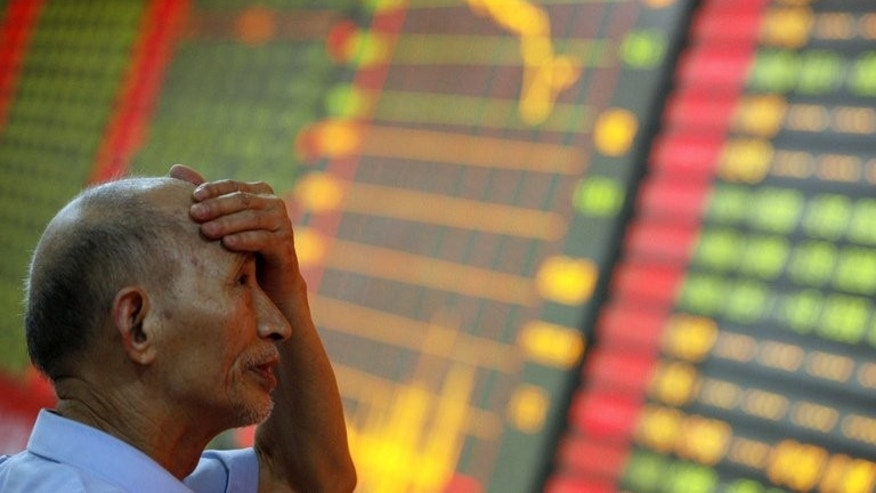 A man gestures as he watches stock activity at a stock exchange in Huaibei, north China's Anhui province on June 24, 2013. Chinese stocks closed at a level unseen since the global financial crisis in 2009 on Tuesday, as analysts warned a liquidity squeeze was raising the risk of a hard landing for the world's second largest economy.