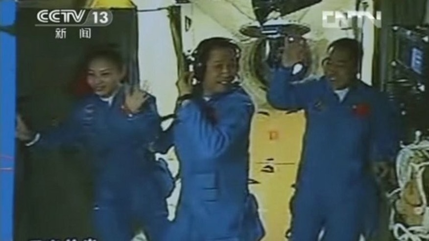 Chinese astronauts (L-R) Wang Yaping, Nie Haisheng and Zhang Xiaoguang waving after they entered the Tiangong-1 space module on June 13, 2013. China's Shenzhou-10 spacecraft has completed a challenging mission to manually dock with a space module and its three astronauts are expected to return to earth on Wednesday, state media said Tuesday.