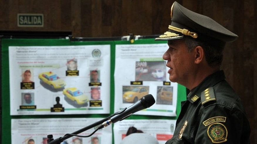 "Colombia's National Police Chief Gen. Jose Roberto Leon Riano speaks next to posters with photographs of four suspects in the murder of the US Drug Enforcement Agency (DEA) agent James ""Terry"" Watson, during a press conference at the headquarters of the National Police in Bogota, on June 25, 2013."