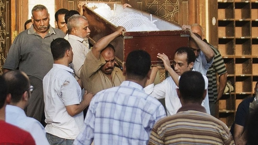 People carry the coffin of a Shiite man killed the previous night by a mob along with three others, during his funeral in El-Sayeda Nafisa Mosque in Cairo on June 24, 2013. Security forces have arrested eight people in connection with the brutal killing of four Egyptian Shiites in a village south of Cairo, officials said on Tuesday.