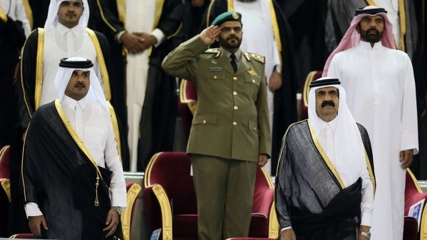 A May 18, 2013 photo shows Qatar's Emir Sheikh Hamad bin Khalifa al-Thani (R) standing next to his son Crown Prince Sheikh Tamim bin Hamad al-Thani (L) before the Emir Cup final between Al-Sadd and Al-Rayyan in Doha. Even before Qatar's emir Sheikh Hamad bin Khalifa al-Thani delivered his early-morning abdication speech on Tuesday, citizens were swearing allegiance to his son.
