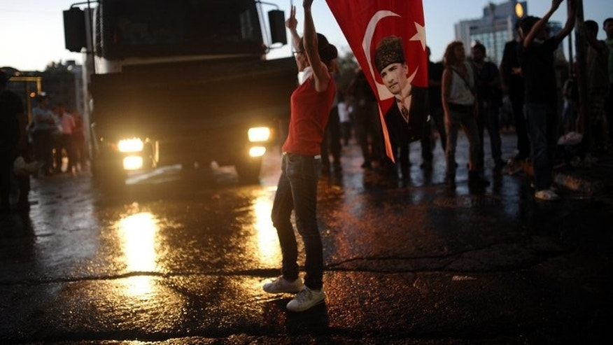 A protester stands in front of a police barricade with a Turkish flag featuring a portrait of Mustafa Kemal Ataurk on it in Taksim Square in Istanbul on June 22, 2013. European Union ministers agreed Tuesday to reopen Turkey's accession talks despite reticence from Germany and others over Ankara's tough crackdown on protests.