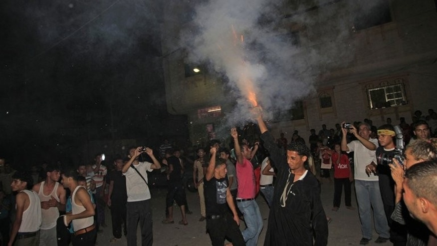"""Fans of Palestinian singer Mohammad Assaf celebrate after he won the final of the Arab Idol competition in front house of Mohammad Assaf in Khan Yunis town in the southern Gaza Strip on June 22, 2013. Thousands of Gaza residents on Tuesday gathered at the Rafah border crossing with Egypt, eagerly awaiting the arrival home of a 23-year-old Palestinian who won this year's """"Arab Idol""""."""