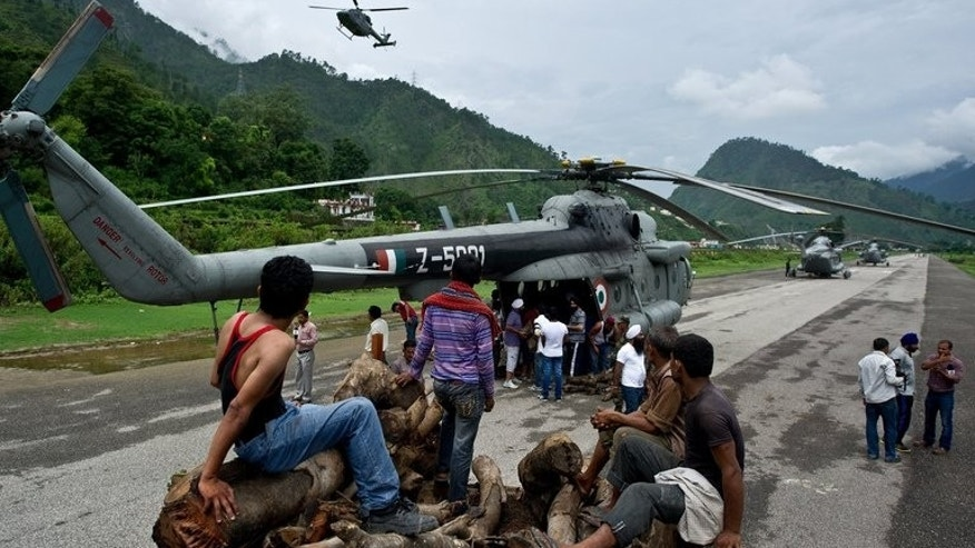 Indian workers wait to offload wood to be carried by an Indian Air Force (IAF) helicopter at Gauchar Airfield on June 25, 2013, ahead of cremation preparations for flood victims in the northern state of Uttarakhand at Kedarnath. Indian officials stepped up Tuesday efforts to prevent an outbreak of disease in the northern Himalayan region devastated by landslides and flash floods.