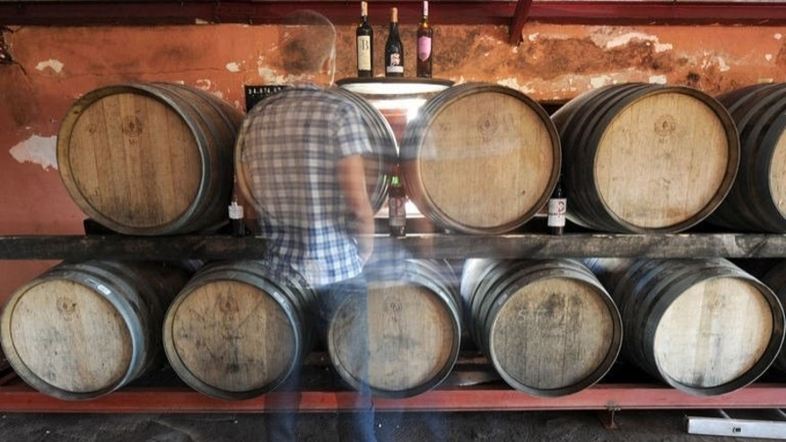 A man walks past wine barrels inside a cellar in the Moroccan town of Benslimane in the Casablanca region, June 12, 2013. Vines stretch to the horizon under the hot summer sun in a vineyard near Casablanca, one of the oldest in Morocco, where despite the pressures from a conservative Muslim society, wine production -- and consumption -- is flourishing.
