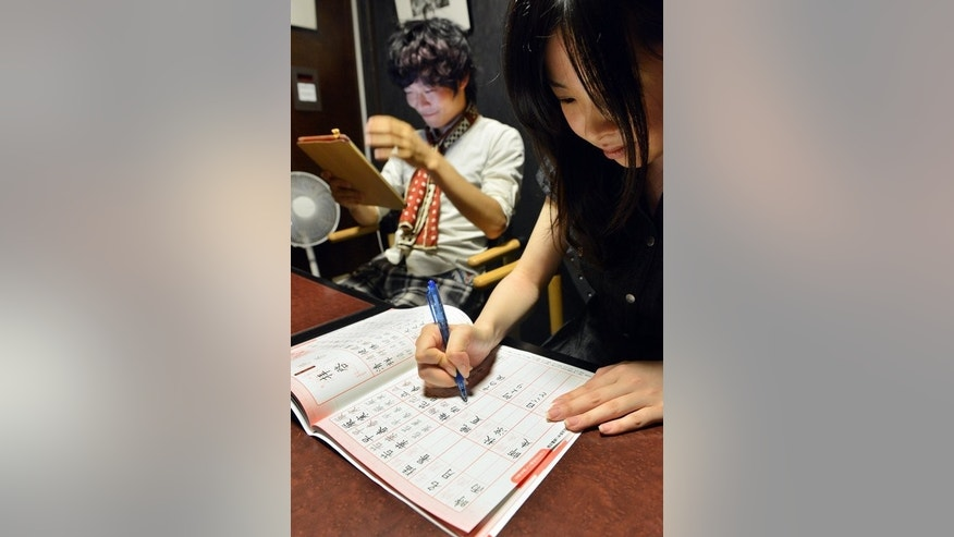 Akihiro Matsumura (L) uses his tablet computer as his friend practices writing Chinese characters in Tokyo on June 19, 2013. Like millions of people across East Asia, Matsumura is forgetting the pictographs and ideographs that have been used in Japan and greater China for centuries.
