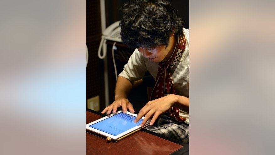 University student Akihiro Matsumura writes sentences on a tablet computer in Tokyo on June 19, 2013. In both Chinese and Japanese, computer and smartphone users need only to type the pronunciation of the kanji from the constituent sounds using either the syllabary or the alphabet.