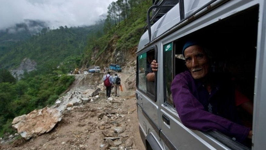 An elderly Indian man looks out as he drives past a damaged section of road between Rudraprayag and Gauchar, at Gauchar on June 25, 2013, after flash flooding hit the northern Indian state of Uttarakhand. An Indian television journalist reporting on the deadly floods that have swept northern India defended his decision on Tuesday to file a report while perched on a survivor's shoulders.