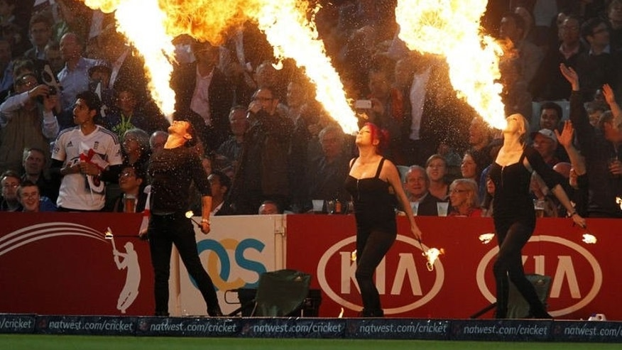 The crowd are entertained by fire eaters during the first T20 International cricket match between England and New Zealand at The Oval cricket ground in London on June 25, 2013. New Zealand won by five runs.