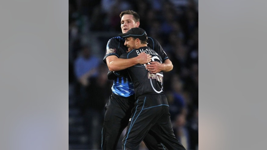 New Zealand's Mitchell McClenaghan (L) celebrates with New Zealand's Captain Brendon McCullum after taking the wicket of England's Luke Wright for 52 runs during the first T20 International cricket match between England and New Zealand at The Oval cricket ground in London on June 25, 2013. New Zealand won by five runs.