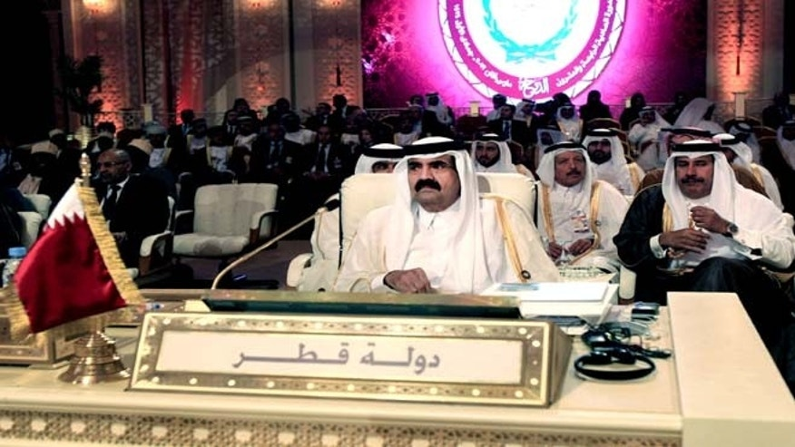 In this Tuesday, March 26, 2013 file photo, Emir of Qatar Sheik Hamad Bin Khalifa Al Thani, center, attends the opening session of the Arab League Summit in Doha. Qatar's emir has moved to hand power over to his son, aiming to bring a youthful new face to rule in a tiny Gulf nation that has become one of the most powerful in the Middle East, aggressively spreading its influence through cash.