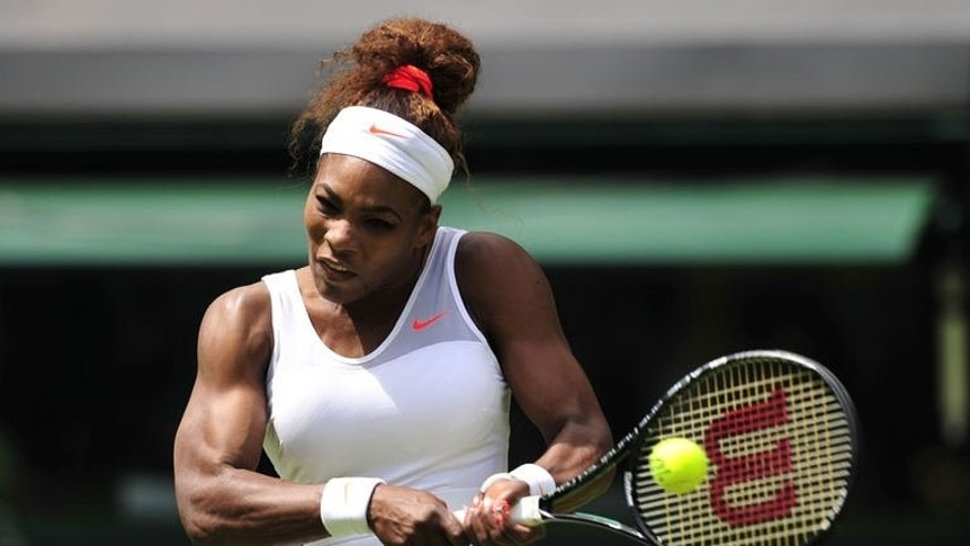 US player Serena Williams hits a return against Luxembourg's Mandy Minella during their women's first round match at the Wimbledon Championships in southwest London, on June 25, 2013. Williams reached the second round with a 6-1, 6-3 win over Minella.